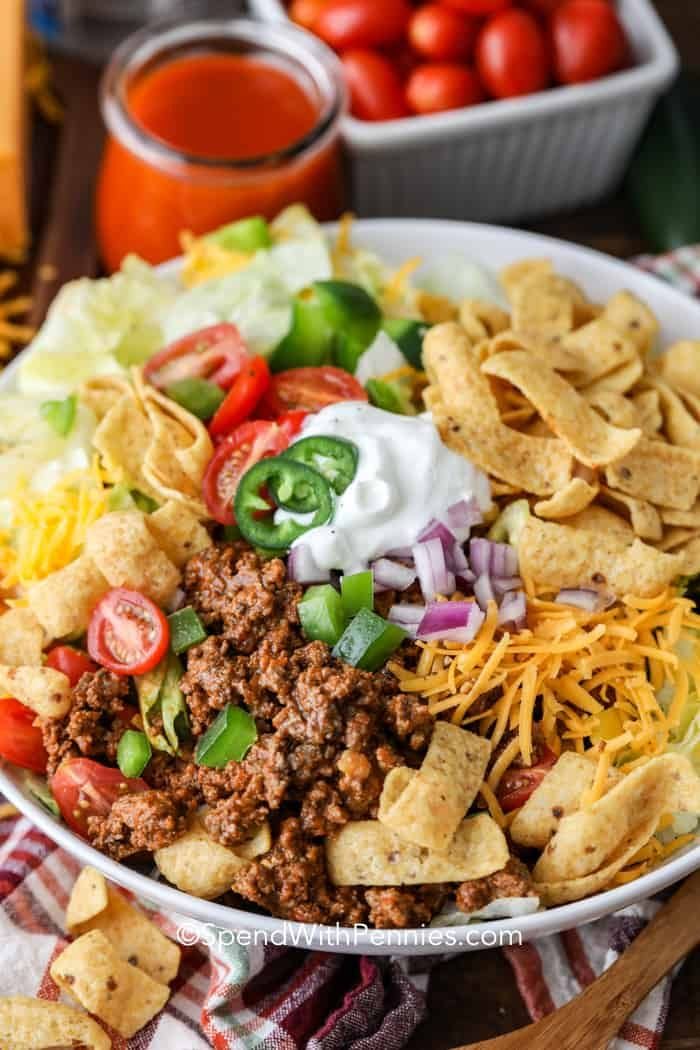 Turn this Frito Taco Salad recipe into a build your own taco salad bar! Set out your ground beef mixture, lettuce, dressings, and toppings and let everyone assemble their perfect taco salad! #spendwithpennies #fritotacosalad #tacotuesday #maindish #salad #tacosalad