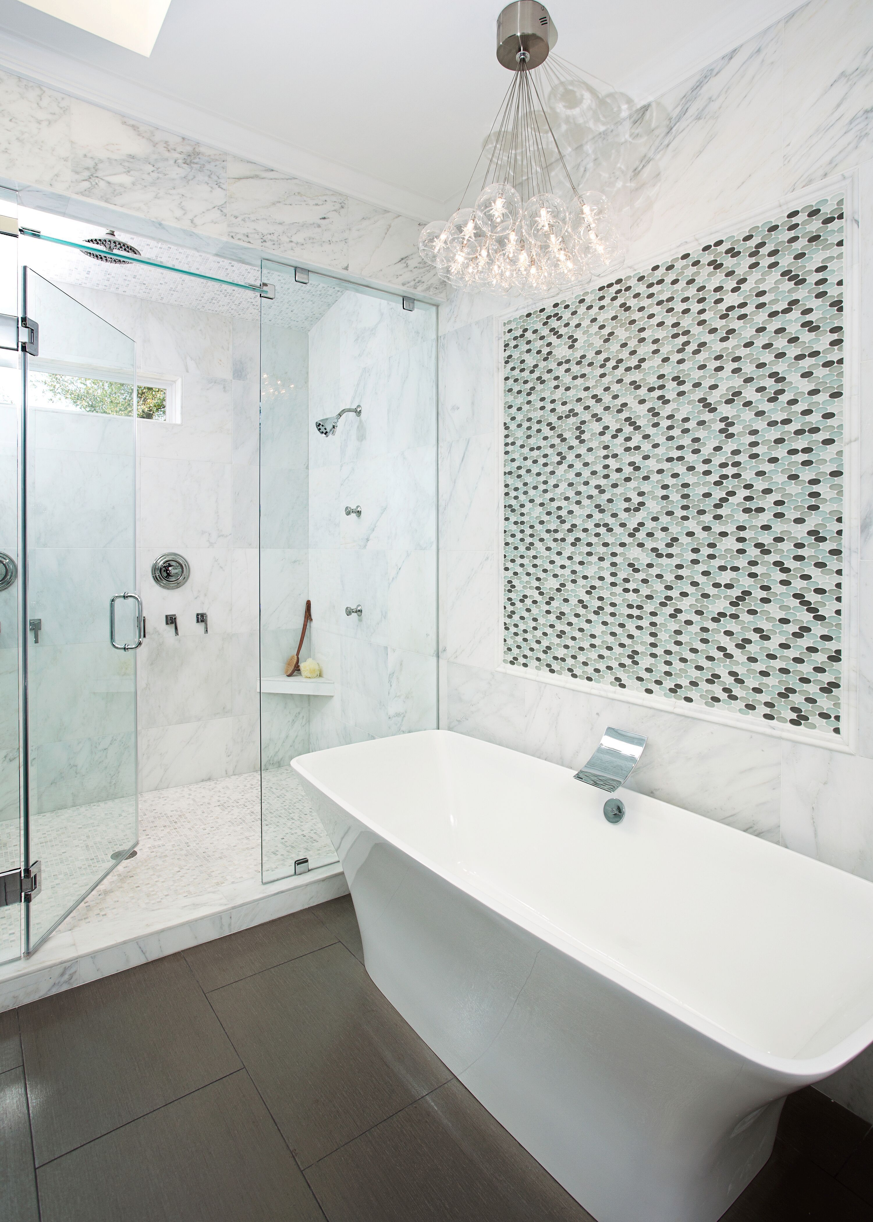White Marble Bathroom With Dark Floors And A Freestanding Tub With