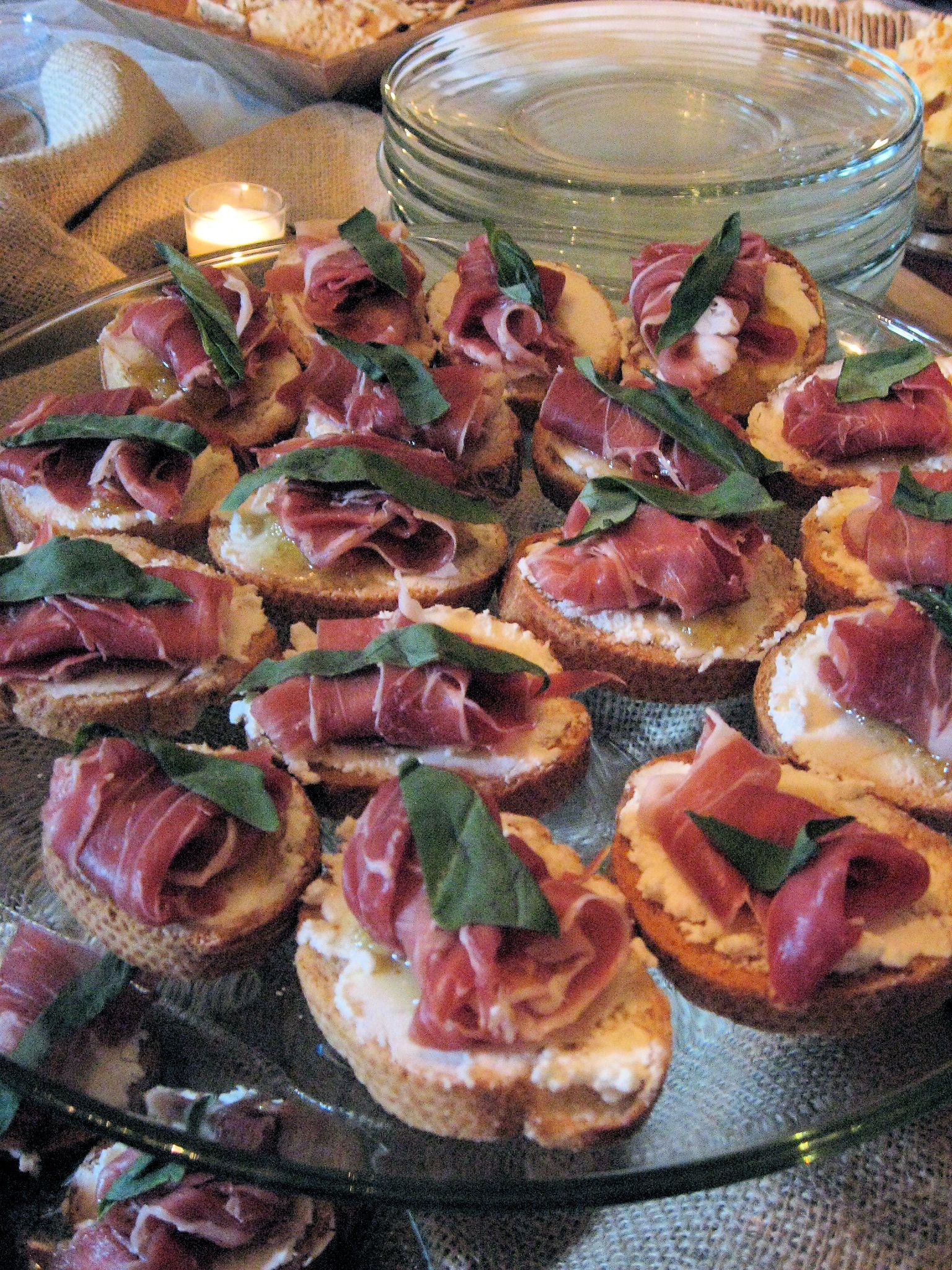 Prosciutto, Fig, and Goat Cheese Crostinis, topped with a fresh basil leaf