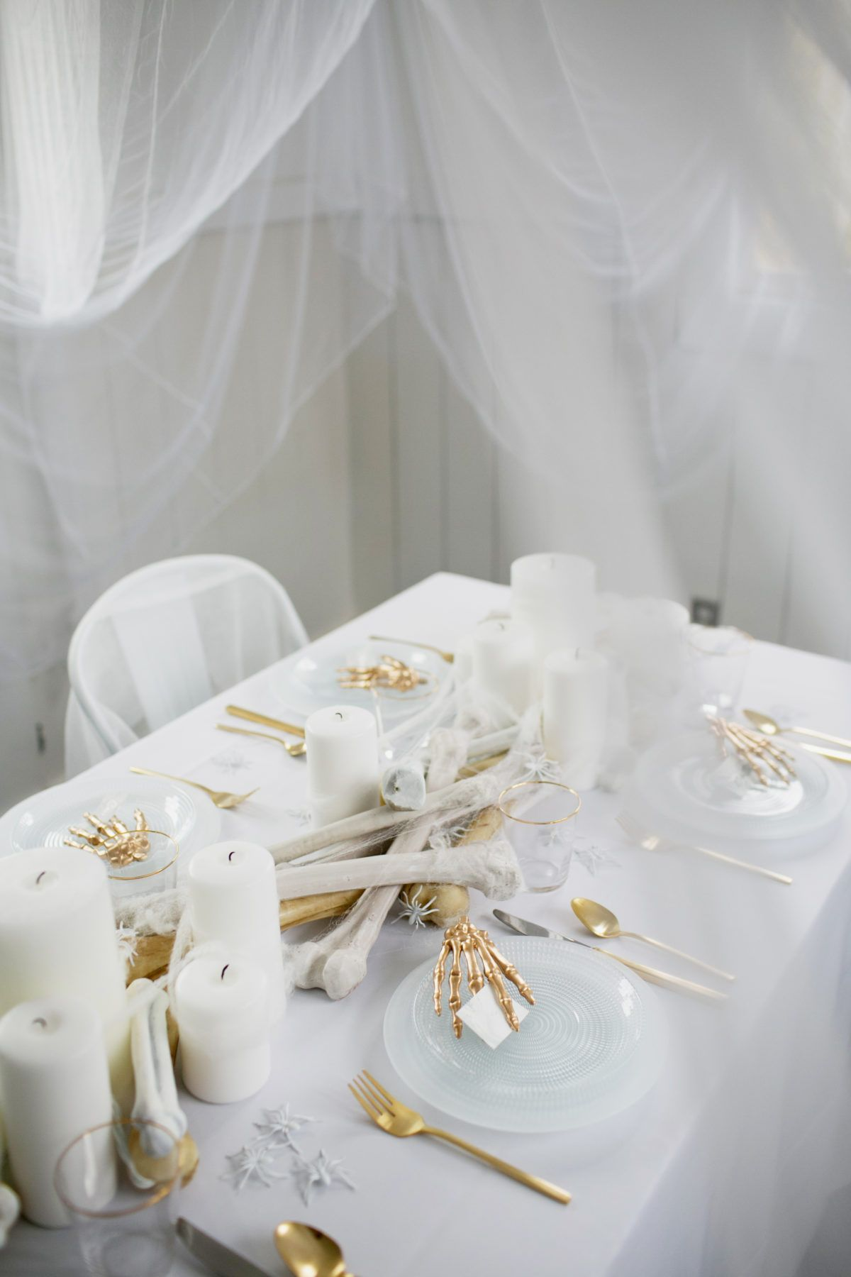an all white ghostly halloween tabletop with bone and candle ...