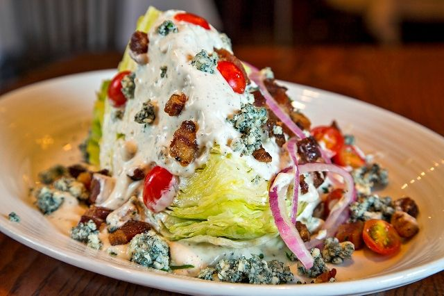 Blue Cheese Wedge: Fresh quarter cut of ice berg lettuce, apple wood smoked bacon, red onion, grape tomato, imported Danish Blue cheese crumbles, and complimented with our signature Danish Blue Cheese dressing.