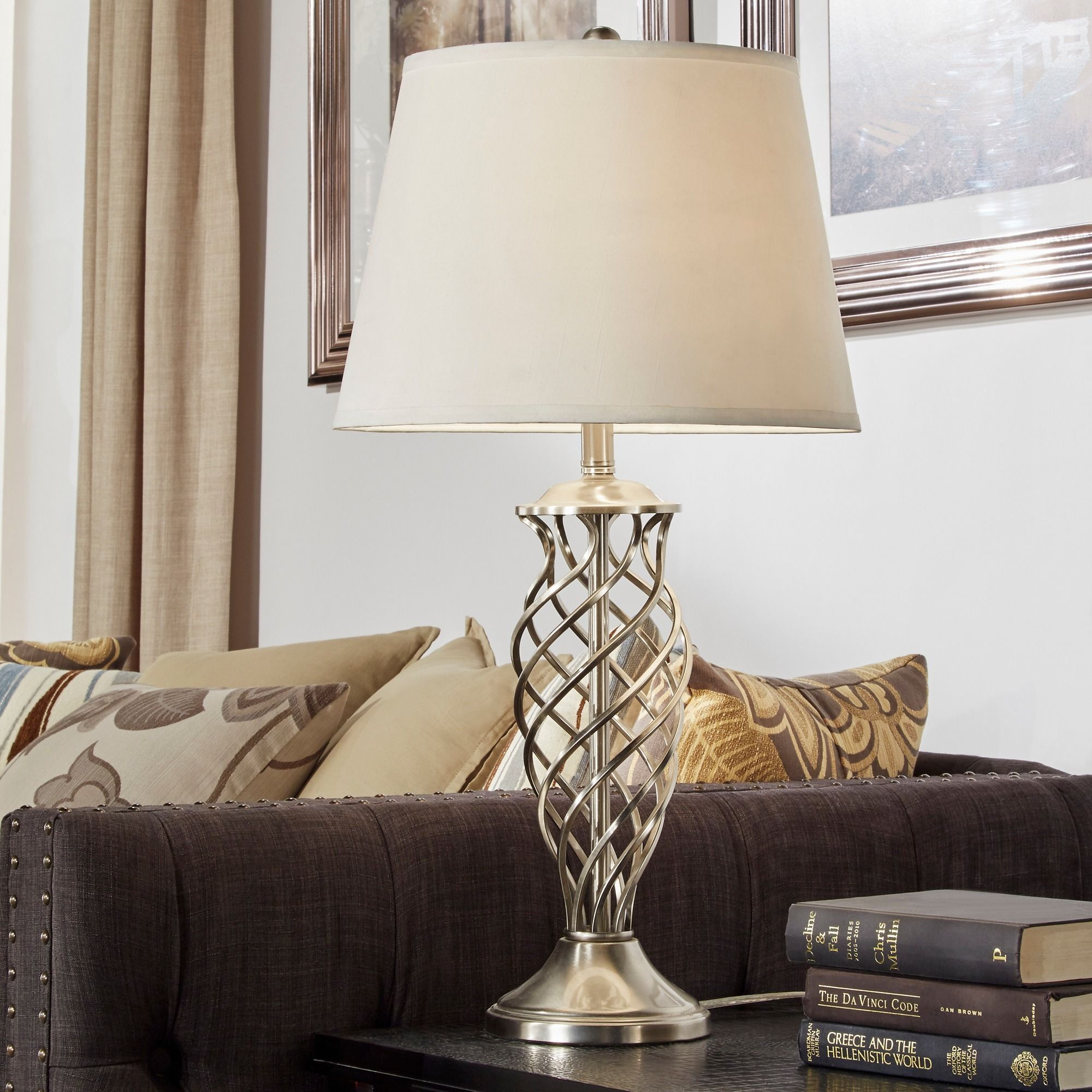 This lamps body is a curved design metallic frame with open space in the middle this showstopping lamp features a contoured base and contemporary fabric