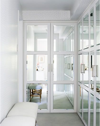 Narrow Walk In Closet With Mirrored Panel Doors Over Clothing