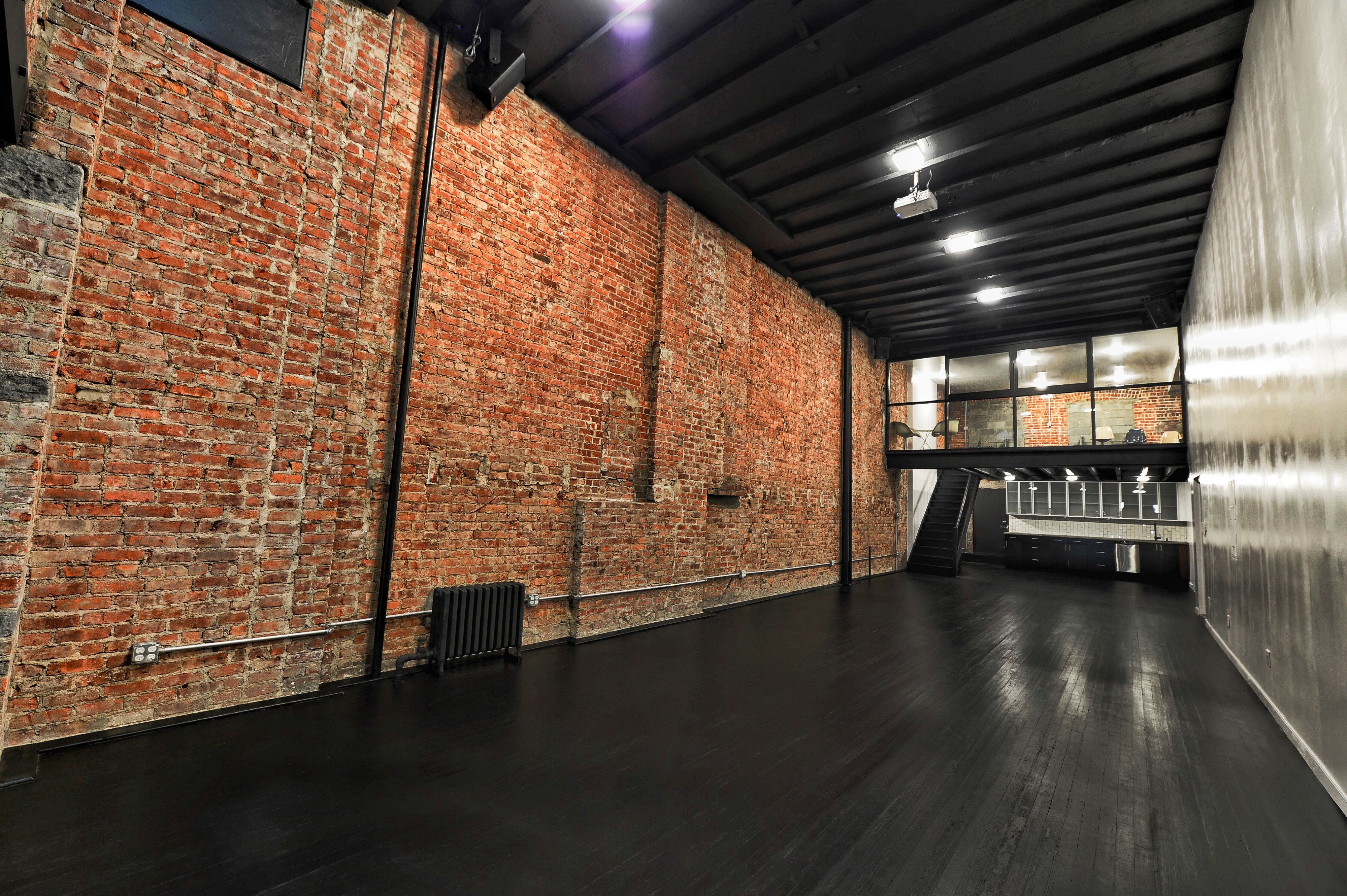 A Creative Loft Studio E Featuring Warm Red Brick Walls Black Wood Floors High Ceilings Large Windows Skylight Creating An Open Modern And