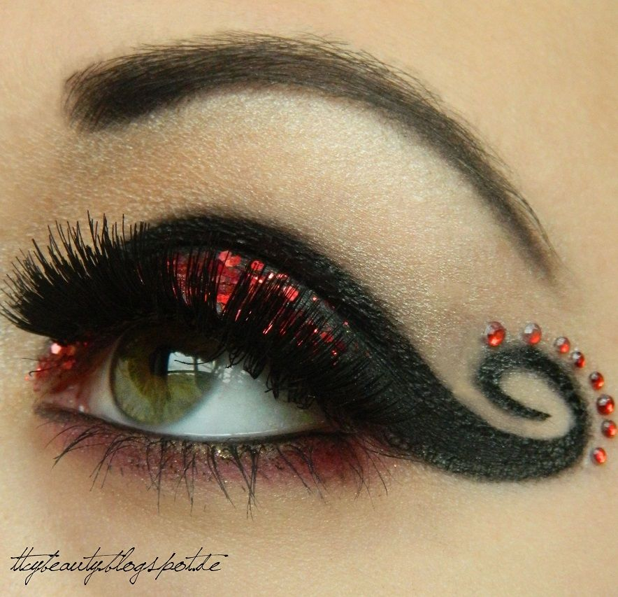 dramatic black swirled eye makeup with red glitter and