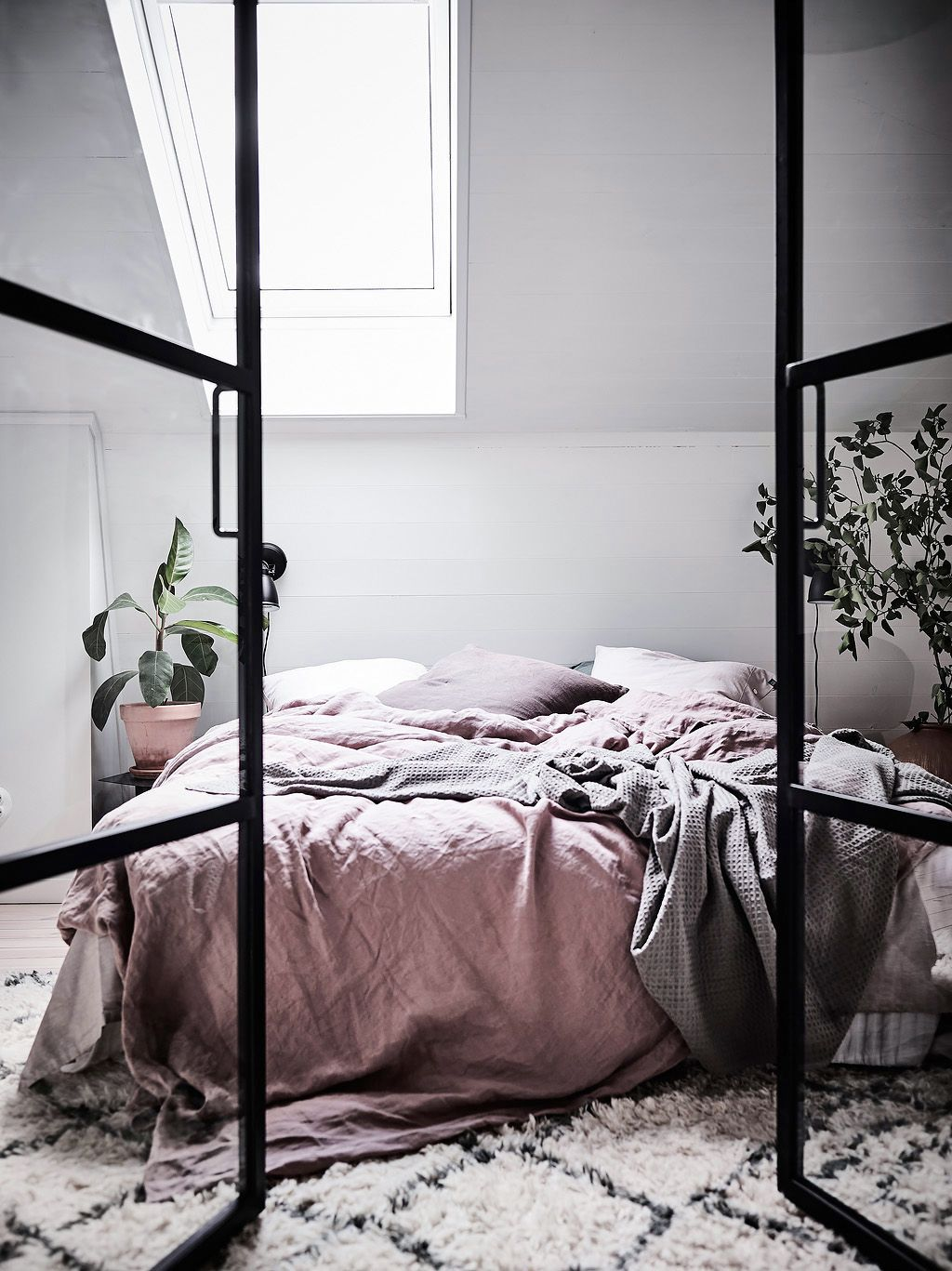 Factory windows open to a sensual pink strewn linen bed cover