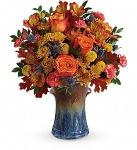 Classic fall colors and a stunning stoneware vase make this arrangement an autumnal favorite! Its glorious orange roses and delicate alstroemeria look oh-so-lovely against the bold cornflower blue and rich bronze hues of this hand-glazed vessel. A gift that keeps on giving, it later becomes an elegant kitchen utensil holder.