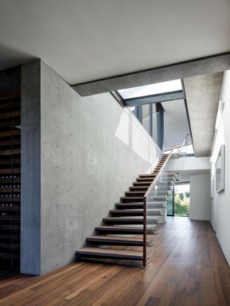 Die Beton Wände im Flur stellen einen Kontrast zum Walnussparkett - design treppe holz lebendig aussieht