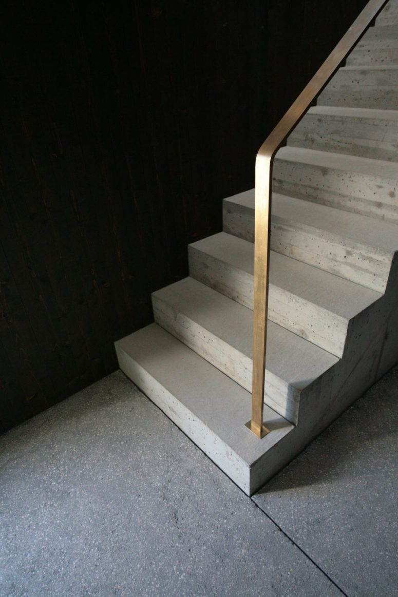 The Staircase Is Concrete With Minimalist Brass Rails Staircase