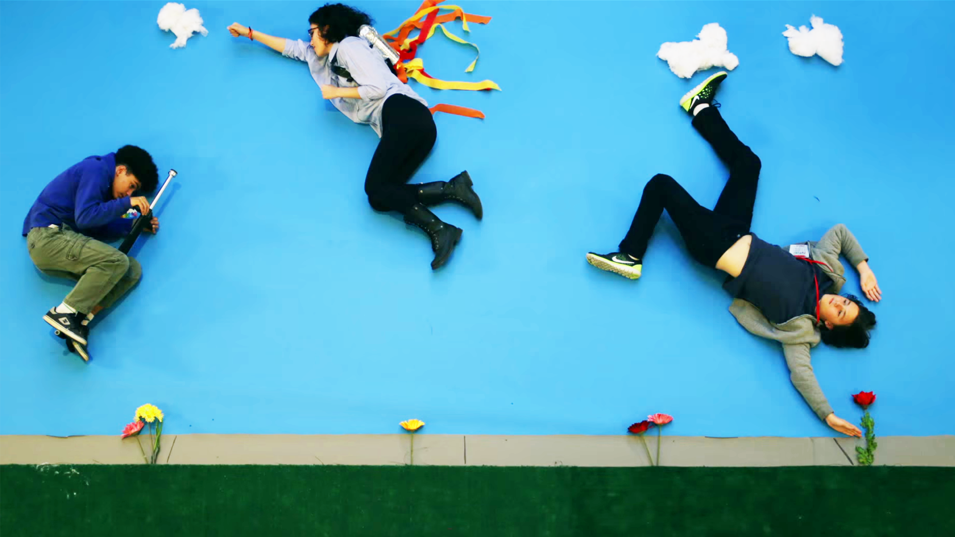 degli attori sono sdraiati a terra il pavimento è celeste come il cielo, la telecamera che li riprende è fissata al soffitto