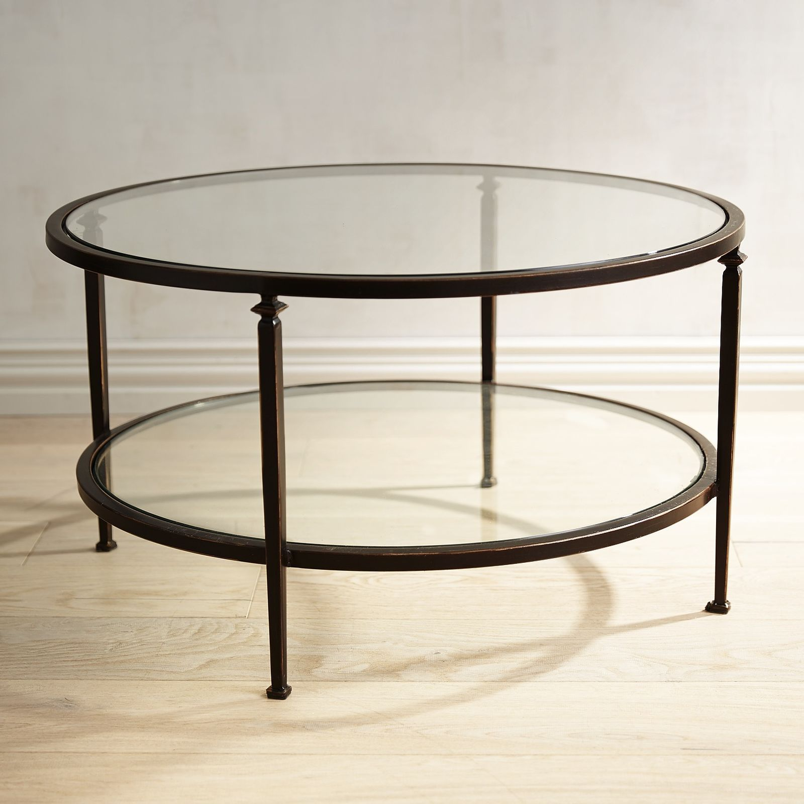 our lincoln round coffee table has a slender bronze wrought iron