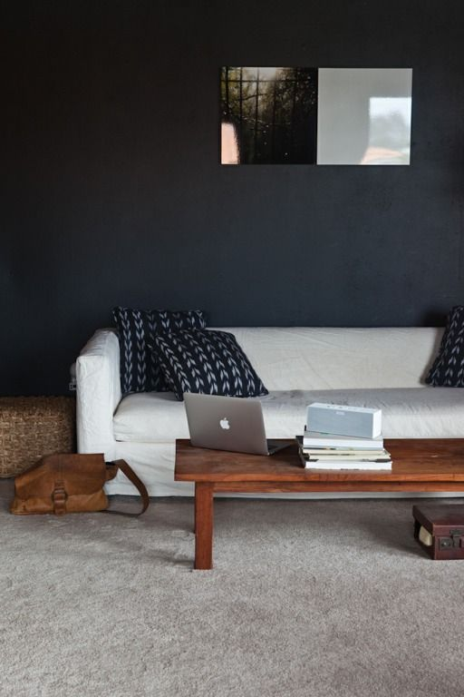 Wood Coffee Table, Plush Carpet, Rattan Side Table, Patterned Throw  Pillows, Dark Walls
