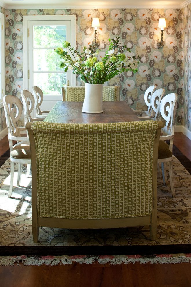 transitional dining room white painted French dining chairs large green cushions with motifs flower wallpaper area rug with motifs dark hardwood floors of