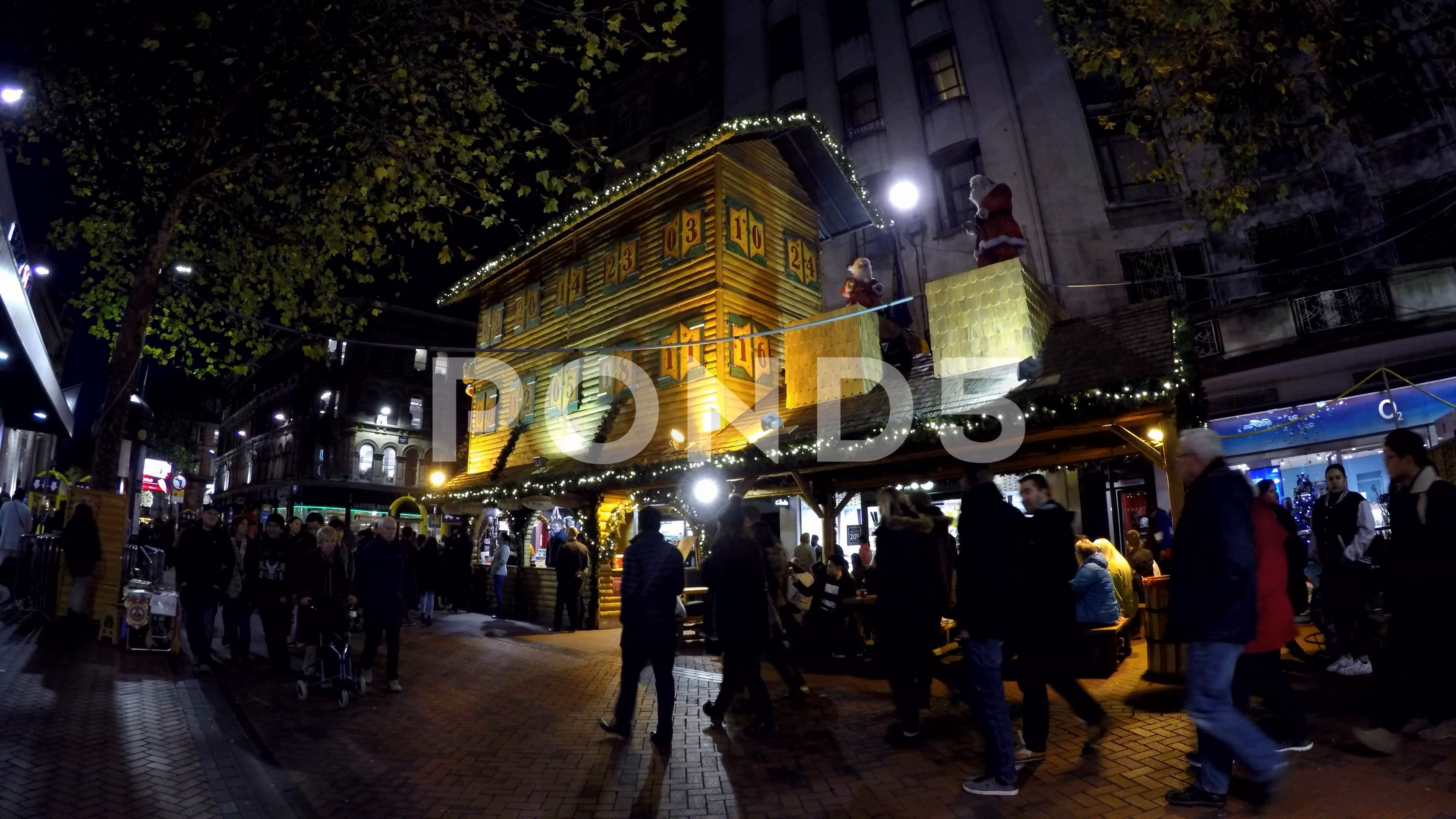 People Walking Past Birmingham German Christmas Market Stalls At
