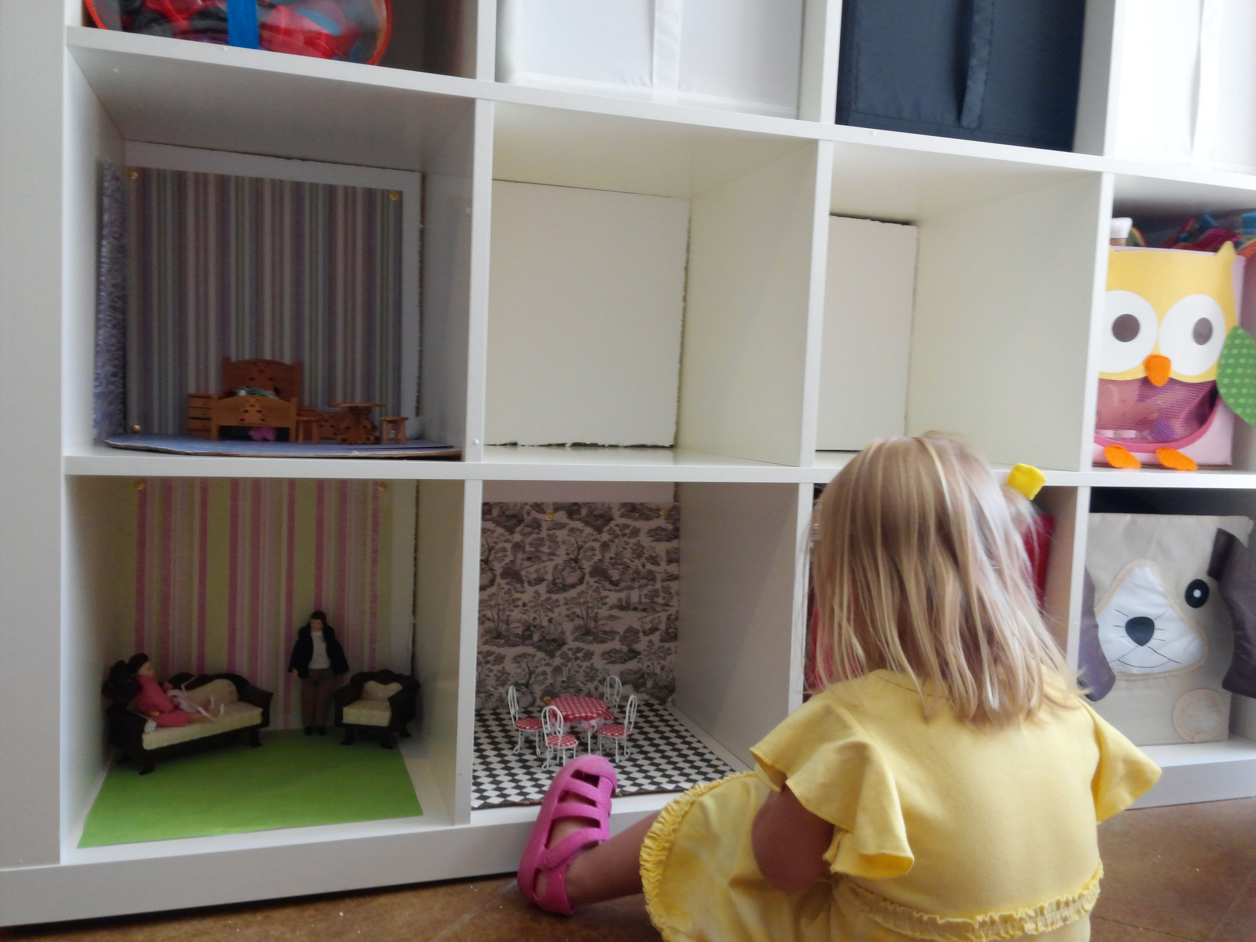Turning some shelves into a dollhouse. Three rooms almost done one bedroom and the outdoor playground to go.  I put Styrofoam on the back to keep things from falling down behind the shelf. The wall paper and carper are just scrapbook paper.