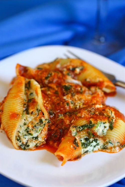 Cheesy Spinach Stuffed Shells12 oz box jumbo shells 1 15-oz container ricotta cheese 1 cup Italian blend grated cheese 3/4 cup grated Parmesan cheese 12 oz cottage cheese 1 tsp salt 1/4 tsp pepper dash of ground nutmeg 24 oz of your favorite marinara sauce 1 1/2 cups grated mozzerella cheese 10 oz frozen spinach, defrosted with liquid wrung out