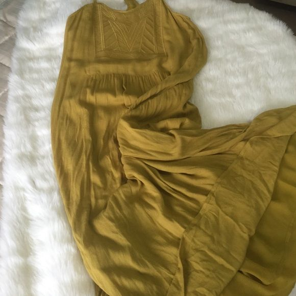 "Modish One Gold Maxi Sundress This beautifully simple maxi sundress is 17"" across from side to side. It says xsmall but very flowy. It is fully lined in smooth polyester and maxi dress, polyester with more texture is gold colored and has no buttons, snaps or zippers. This comfort and beauty! The dress is brand new, never worn and in perfect condition. The raised design in front is quite stunning. You will be the belle of the ball in this lovely summer dress! Modish One Dresses Maxi"