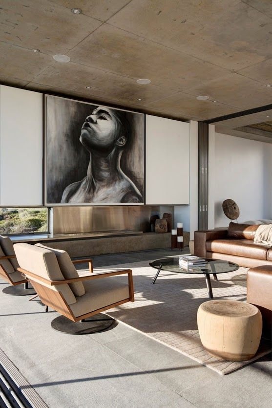 This living room is focused around a fireplace with a large piece of art hanging above it