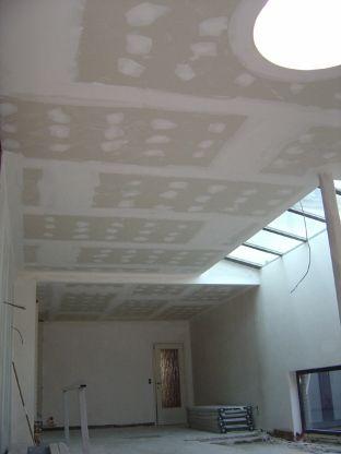 Gyprocplafond living in twee niveau's met een ronde lichtkoepel.