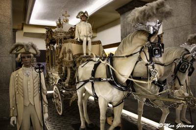 """Museo de Carruajes Fúnebres de Barcelona. Angélica.Carroza blanca de lujo muy parecida a la gótica y también muy elaborada. Servía para el transporte de cadáveres de niños, jóvenes y doncellas. Mayordomos vestidos """"a la federica"""" de color blanco, caballería blanca, todo ello como símbolo de pureza."""