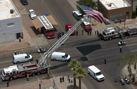The Phoenix Fire Department hoisted a flag above a ladder truck to receive the bodies of the 19 firefighters killed Sunday.