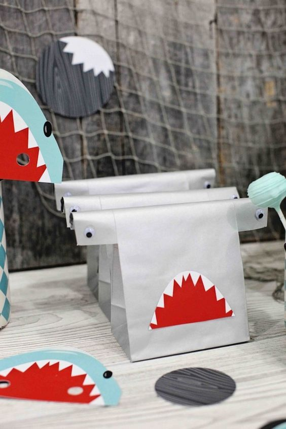 Shark birthday party ideas - the hammerhead favor bags and shark fin cake pops are great ideas.