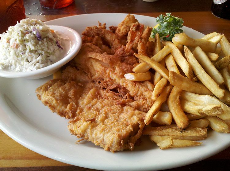 A Plate Of Amberjack Fish Shrimp Fries And Slaw At The Back
