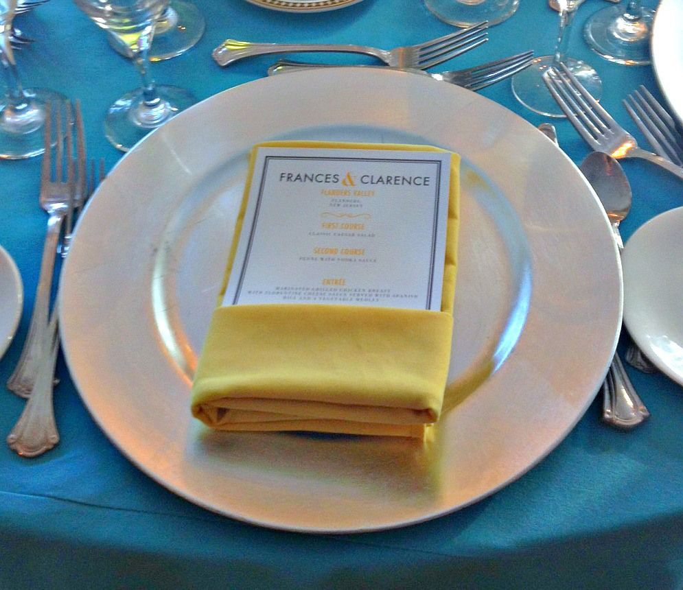 Silver chargers with yellow napkins and turquoise linens.