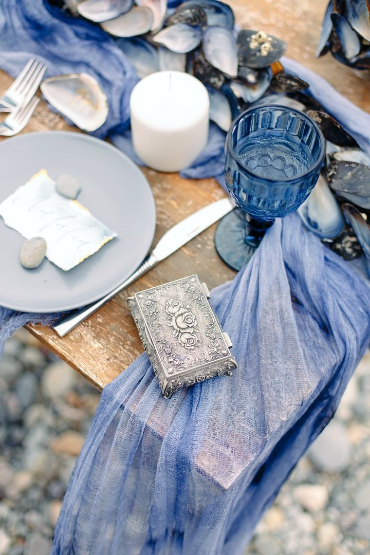 Beach wedding table setting in shades of ocean blue with linen table runner + white candles + mussel shells table runner | fabmood.com #weddingtable #weddingtablescape #tablesetting #beachwedding #beachtablescape #oceanblue #mistyblue #mistygrey #tablerunner