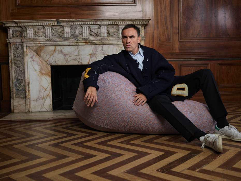 Fashion Designer Raf Simons Sprawls On A SACCO Bean Bag Chair Designed In