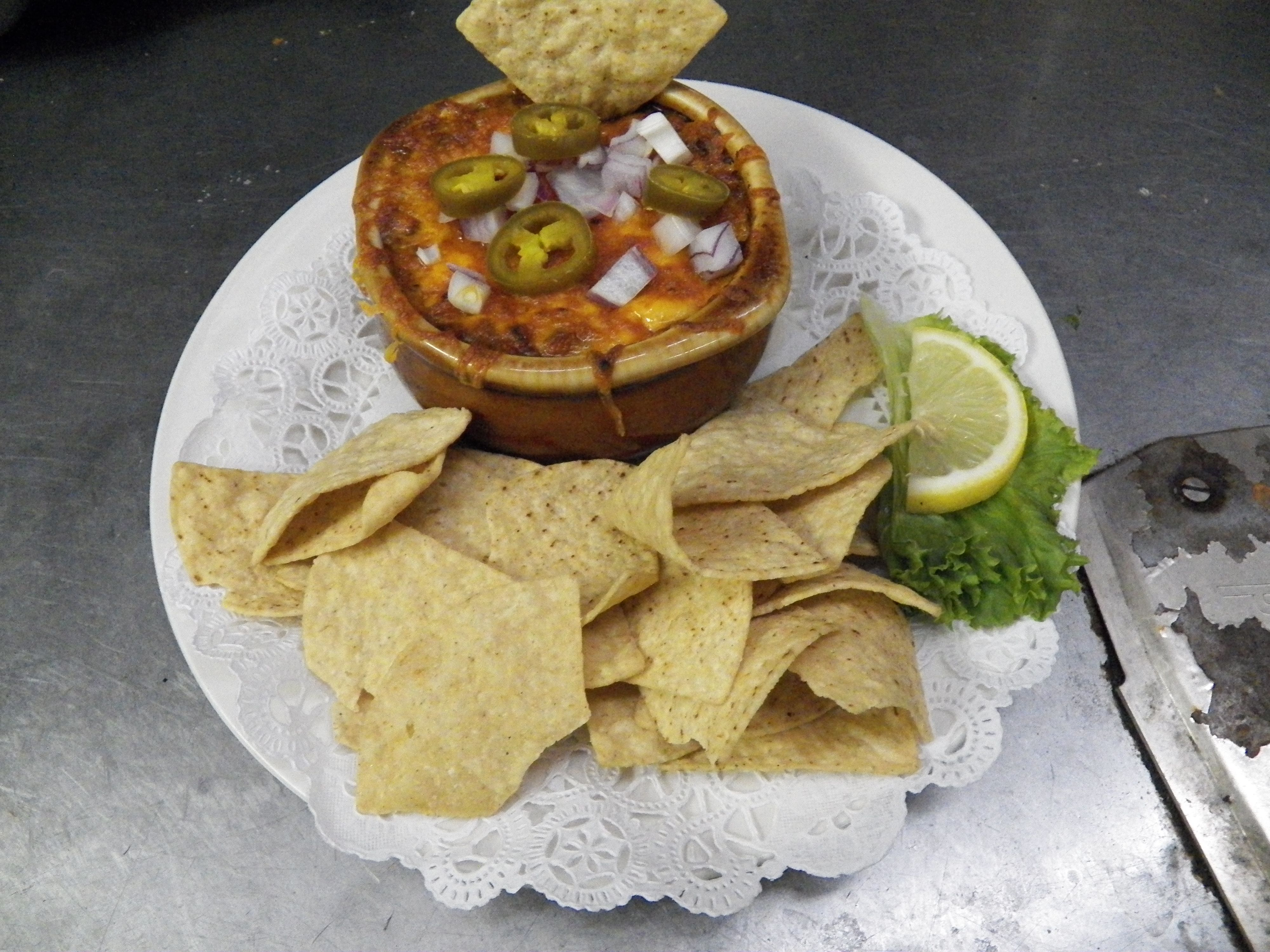 A bowl of our savory chili is perfect for a cool evening at the dockside bar! Topped with cheddar cheese, it is sprinkled with purple onion and chopped jalapenos! Perfectly served with a helping of tortilla chips!