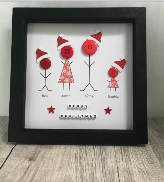A stunning button picture featuring a family of stick people wearing glittery Santa hats.