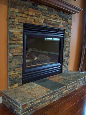 Contemporary raised hearth fireplace designs warm your - Covering brick fireplace with tile ...