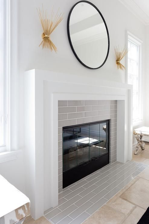 A black convex mirror is illuminated by two kelly wearstler strada 2 light wall sconces placed over a white art deco fireplace mantel accented with linear