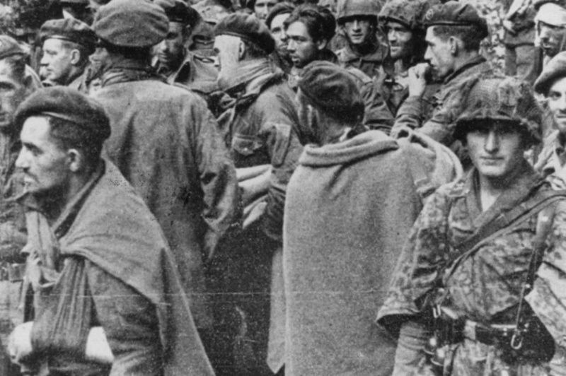 A soldier of the Waffen-SS guarding British paratroopers who were taken prisoner during the battle for the Arnhem bridge, September 1944