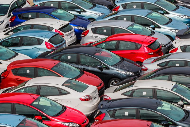 Brand new motor vehicles crowed in a parking lot Waiting for distribution to De