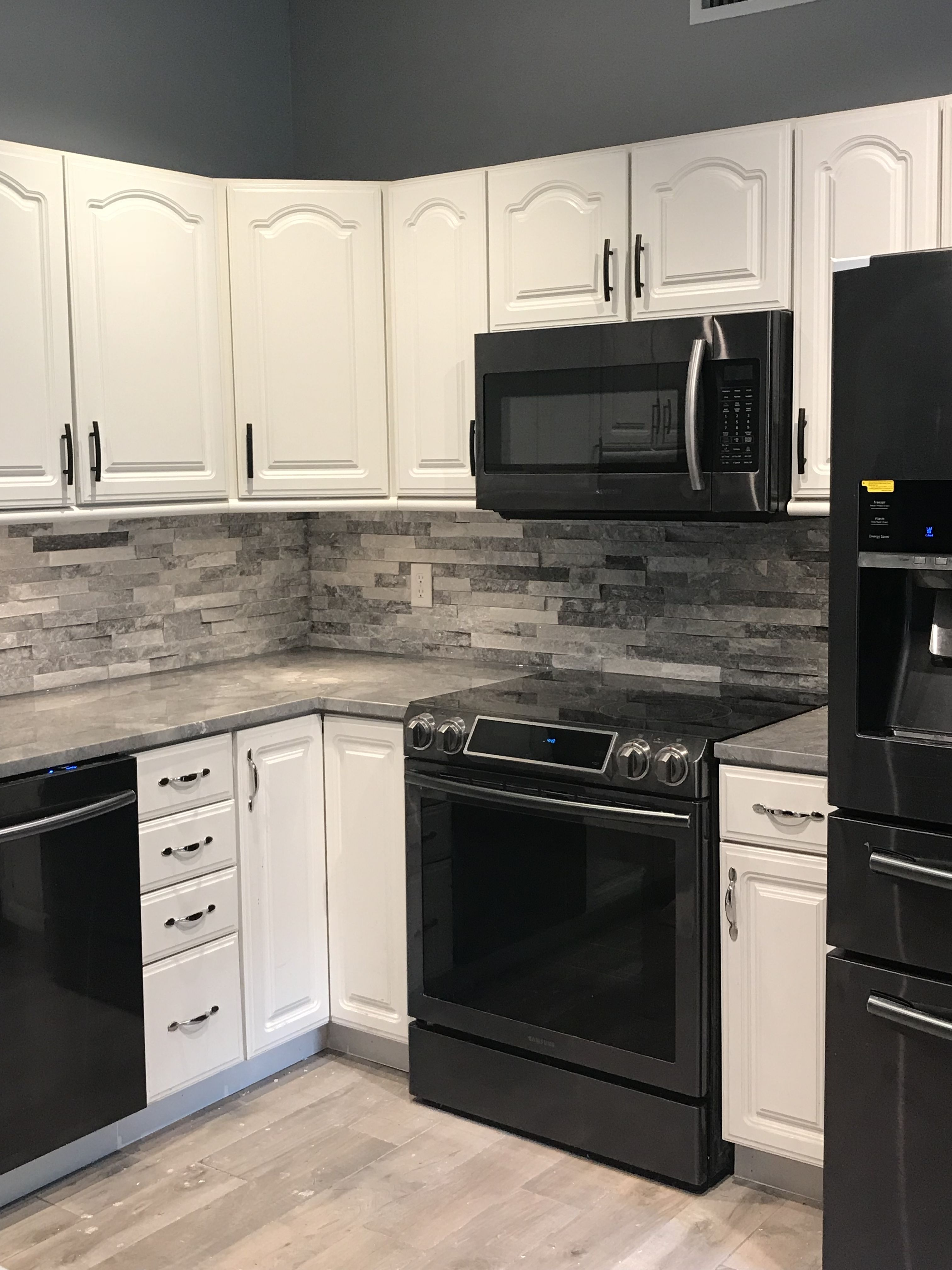 Stackstone backsplash, black stainless appliances White