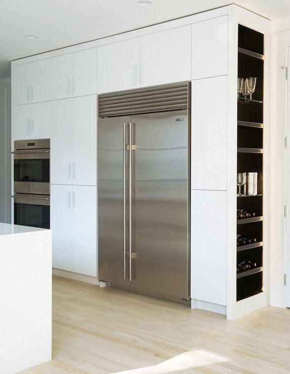 Modern kitchen features a full wall of pantry cabinets fitted with double ovens and a stainless steel refrigerator and freezer alongside end cabinets lined with shelves housing wine glasses and wine bottles. #Diydormroom
