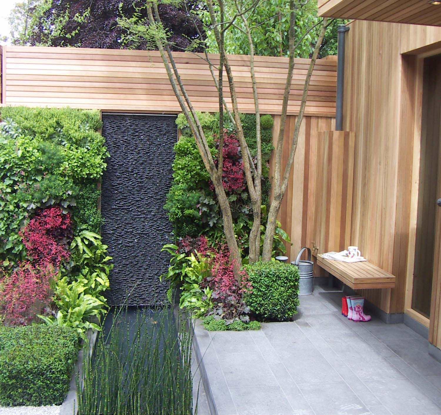 a living wall formed of plants makes a really unusual boundary for this lovely little front garden designed by mark gregory for the chelsea flower show