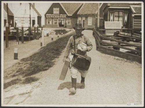 De postbode (tevens telegramjongen enz.) van Marken op zijn dagelijkse route door het dorp 1928