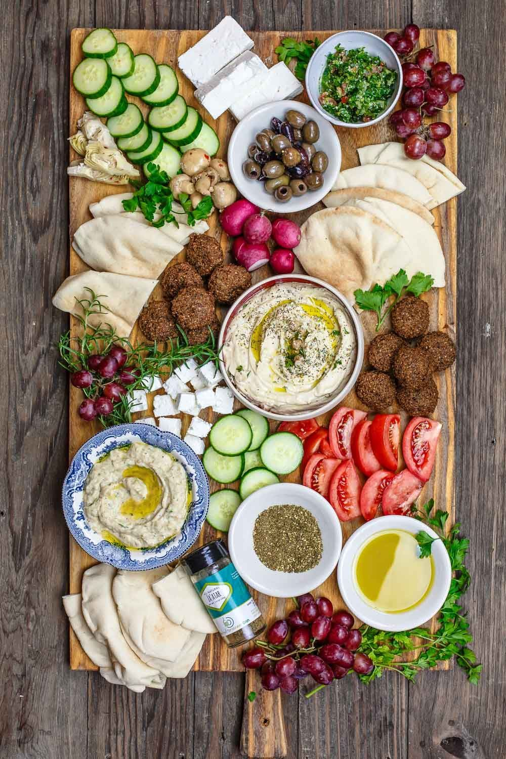 Ultimate Mediterranean Brunch Board from The Mediterranean Dish #grilledshrimp Mediterranean Diet Breakfast Board with falafel, hummus, black olives, feta cheese and veggies, served on a board.