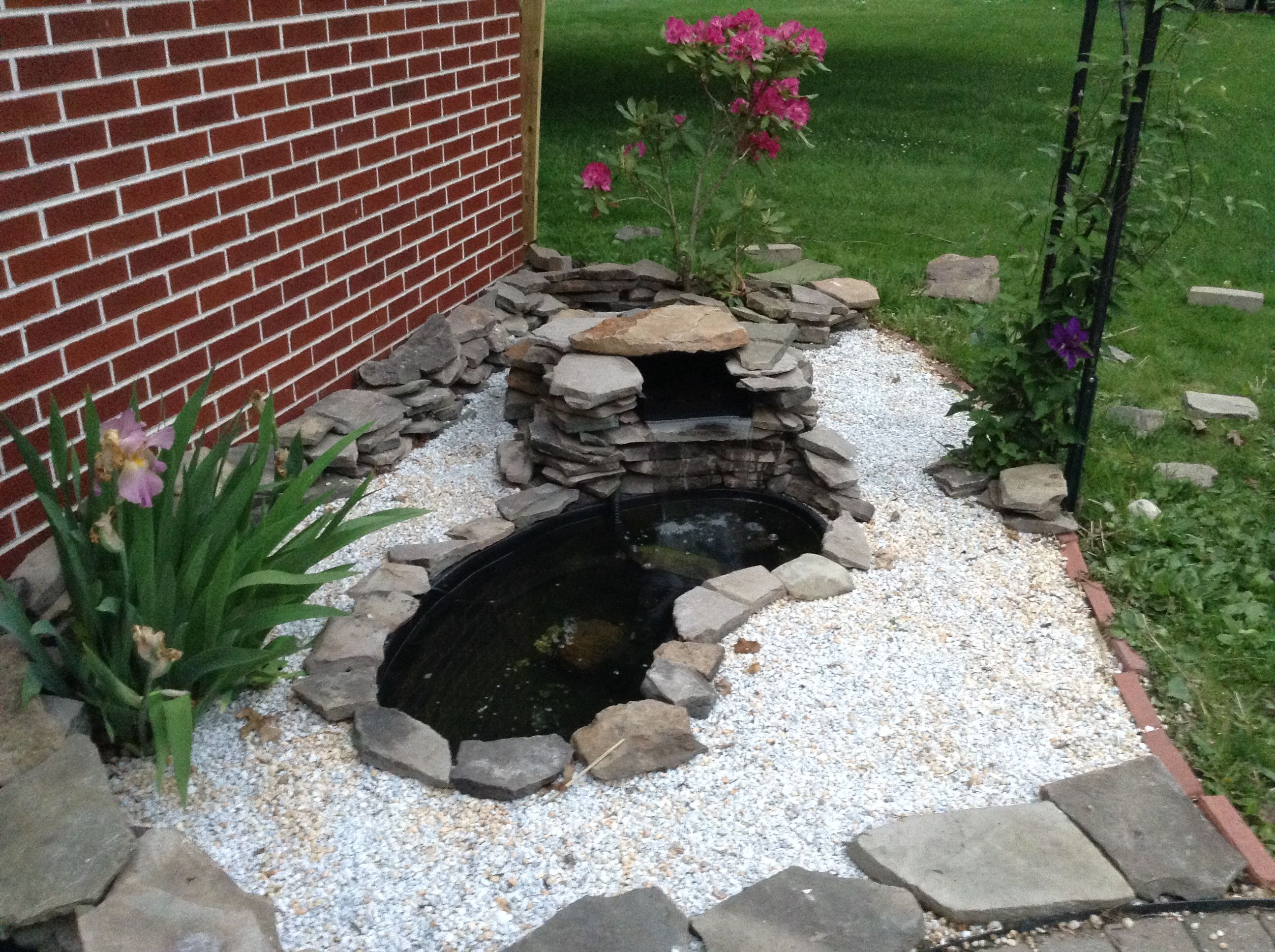 small fish pond with pebbles and stones and waterfall