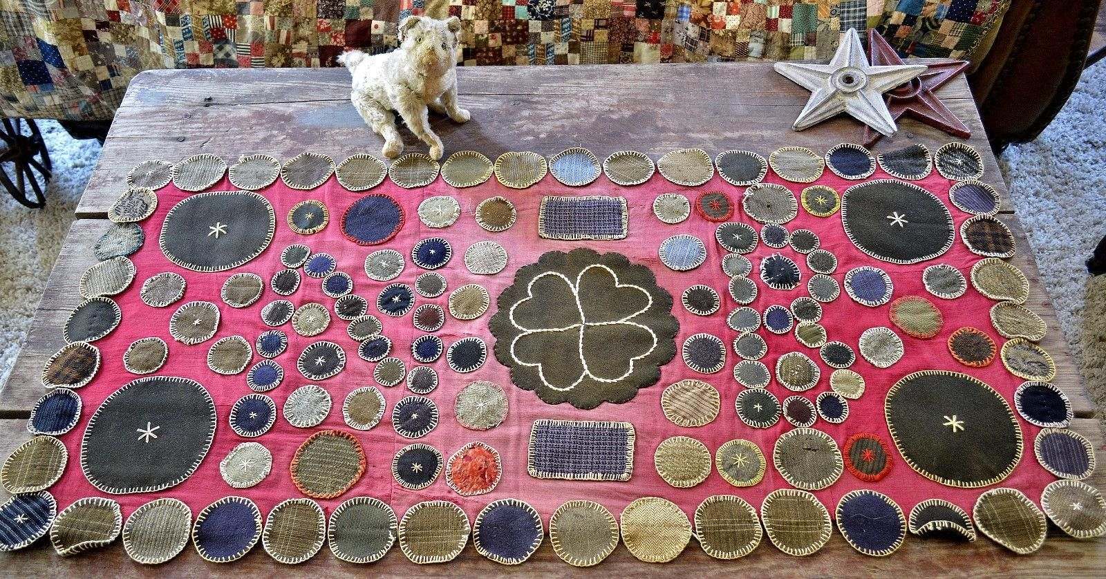 Here is an antique handmade folk art penny rug. The rug is worked on plum cotton cloth with wool circles and shapes which form initials. The backing is woven and there are early patches and repair. T