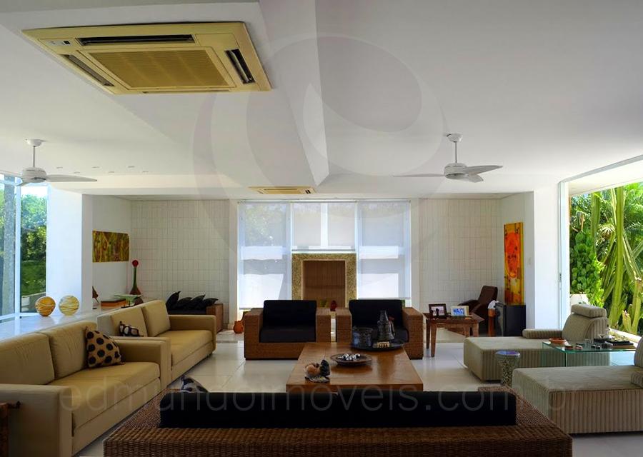 O amplo salão principal integra o living room, decorado com sofás em diferentes tons de bege e poltronas de linhas retas revestidas em fibra natural, com a sala de lareira, em uma composição cheia de charme e estilo.
