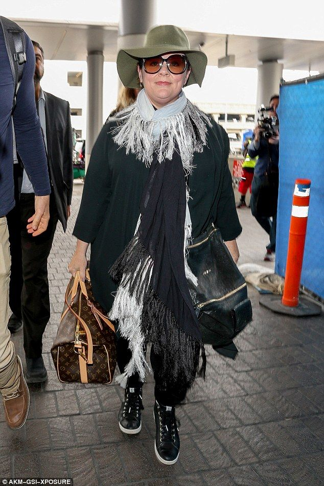 feeling a chill? Melissa McCarthy rugged up in lots of clothing as she flew out of Los Ang...