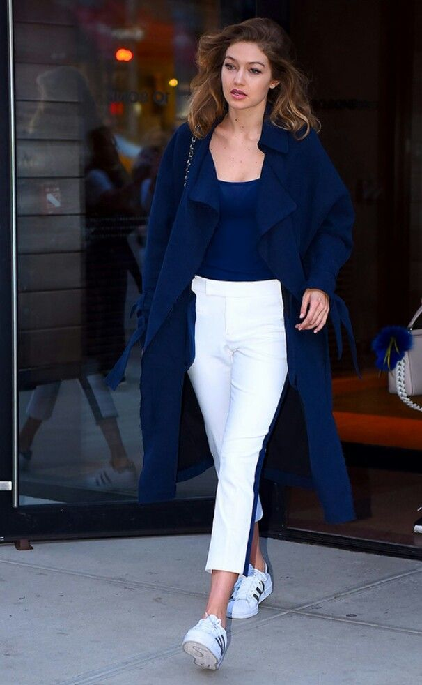 b7163c452a 9 June Gigi Hadid looked sporty in a pair of white tailored trousers and a  blue duster coat as she made her way around New York.