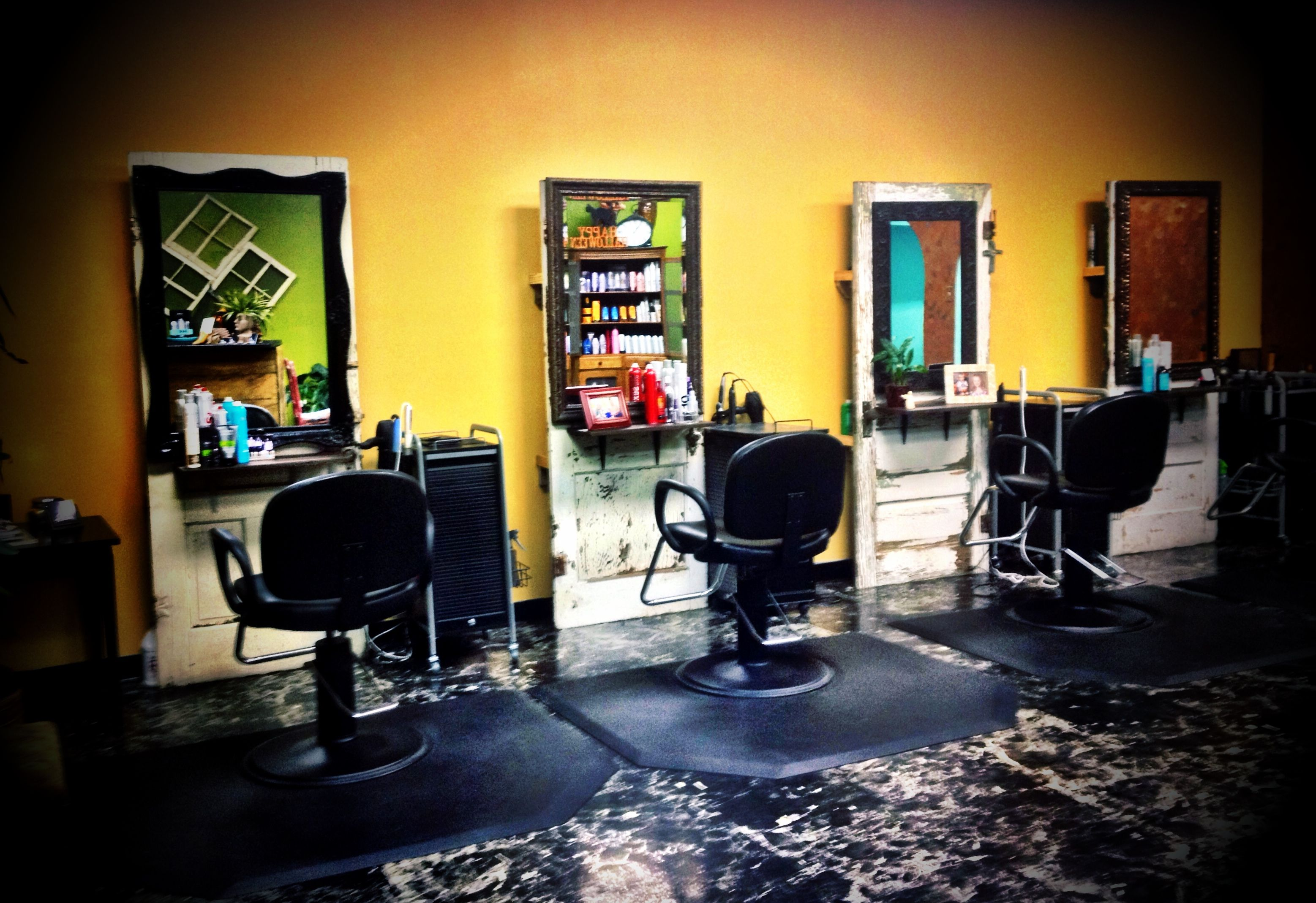 Mirrors hang on antique doors used as styling stations at M Salon. Behind the door shelving was created for additional hidden storage.