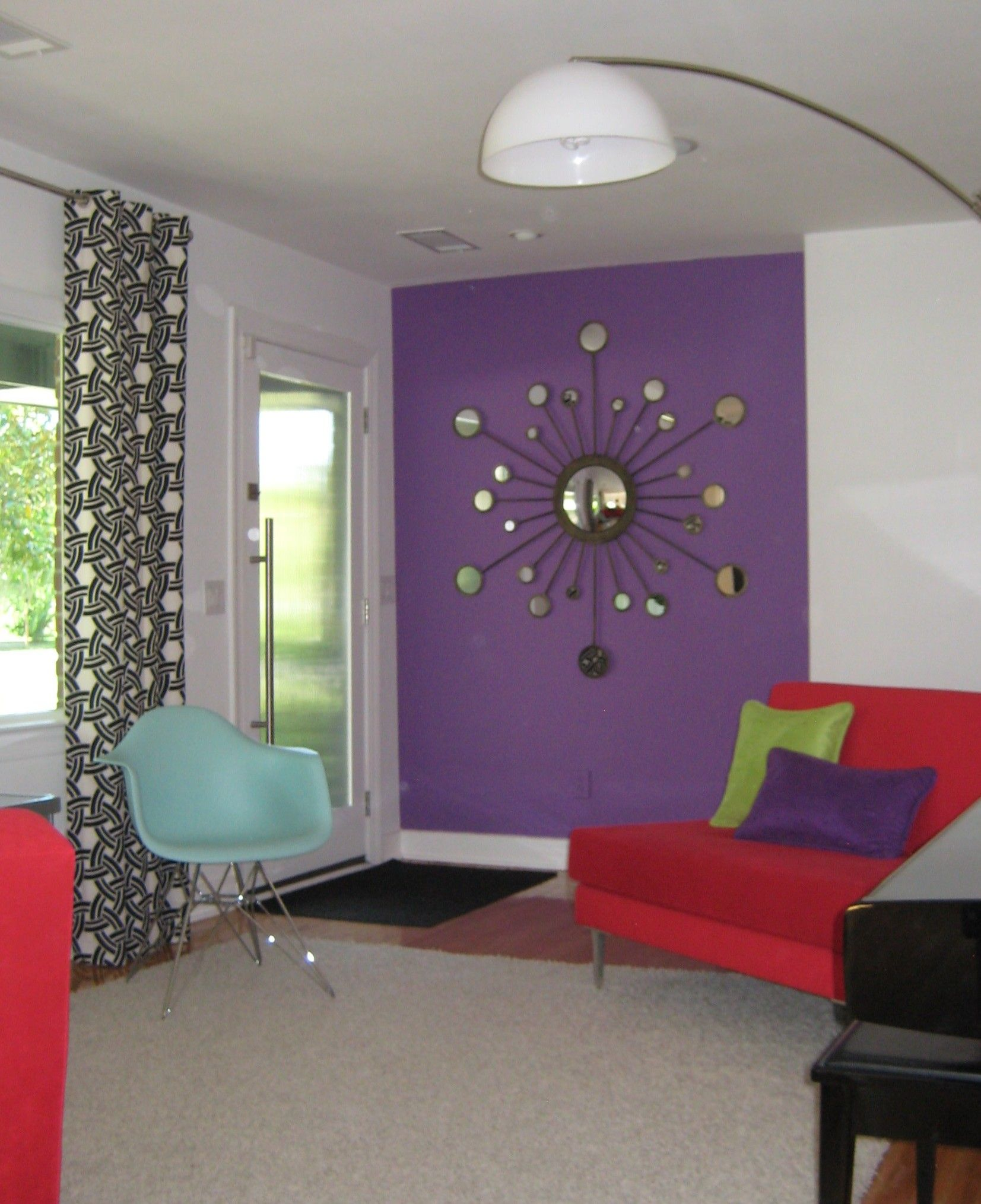 Retro design purple accent wall starburst mirror arc floor lamp red sofas black and white Purple accent wall in living room