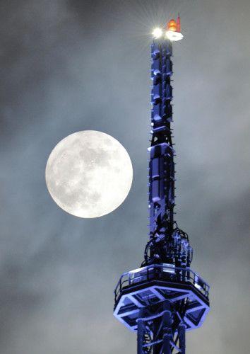 雲間から顔を出したスーパームーン。手前は福岡タワー(14日午後8時6分、福岡市早良区で)=園田寛志郎撮影