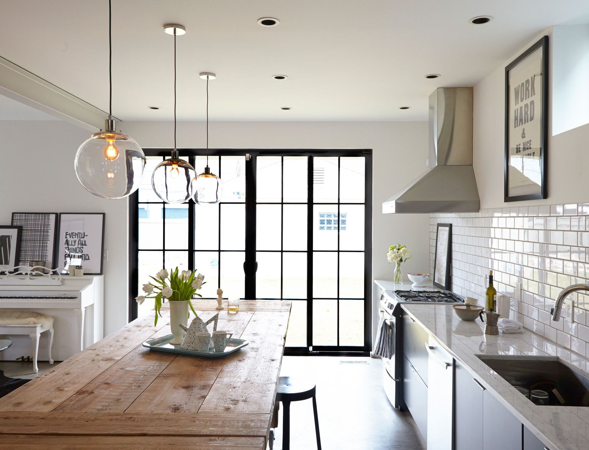 In the clear pendant lighting farming and third three pendant lights from west elm are suspended over a knotty surfaced farm table in the kitchen one of the few holdovers from the homeowners previous aloadofball